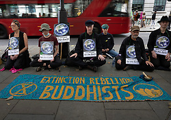 © Licensed to London News Pictures. 25/08/2021. London, UK. Buddhists sit on the pavement as XR (Extinction Rebellion) protesters gather outside the Brazilian Embassy on a global day of action for Indigenous Peoples of the Amazon rainforest. XR are on day three of a planned two week protest in the captital calling for action on climate change. Photo credit: Peter Macdiarmid/LNP