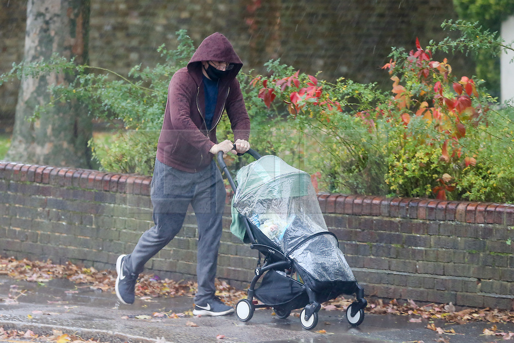 © Licensed to London News Pictures. 31/10/2020. London, UK. A man with a pram during rainfall in north London. Met Office has issued weather warnings from today to Monday for heavy rainfall and strong winds from Storm Aiden and the remnants of Hurricane Zeta. Photo credit: Dinendra Haria/LNP