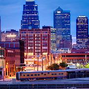 Kansas City, Missouri skyline at dusk, antique train parked in foreground, taken from Washington Square Park.