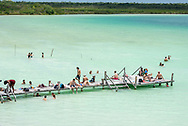 Tulum, Mexico - June 6, 2021: Visitors to Kaan Luum Lagoon outside Tulum enjoy a sunny afternoon in the shallow, tranquil water.