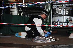 © Licensed to London News Pictures. 22/08/2013<br /> Police officer placing a knife in evidence tube.<br /> A man has been in stabbed in Bexleyheath this evening. Emergency services were called to the Broadway, near McDonalds, at 8.15pm tonight (22.08.2013) <br /> The man, aged in his late 50s, was treated at the scene before being rushed to a south London hospital with a stab wound where his condition is desribed as stable. <br /> A man was arrested in connection with the incident and has in custody in a south London police station. Police have cordoned off a large section of the Broadway following the incident. <br /> Photo credit :Grant Falvey/LNP
