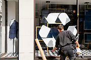 A male retaill contractor pastes a recyclig sticker on to the window surface at the Jermyn Street branch of Charles Tyrwhitt, on 27th April 2021, in London, England. Now that their branches are re-opening after pandemic lockdowns, men's clothing retailer Charles Tyrwhitt are offering a recycling service for old shirts.