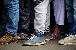 © Licensed to London News Pictures. 24/10/2016. Calais, France. Worn footwear of migrants as they queue to board busses during the evacuation and demolition begins at the migrant camp in Calais, known as the 'Jungle'. French authorities have given an eviction order to thousands of refugees and migrants living at the makeshift living area of the French coast. Photo credit: Ben Cawthra/LNP