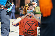 A detained member of Extinction Rebellion Youth Cambridge gestures as she wait to be taken by the police after she was involved in a road block action outside Baringa Partners building in London on Thursday, Sept 10, 2020 - in an attempt to highlight the involvement of Schlumberger Limited in what they call 'ecocide'. Schlumberger is an oilfield services company working in more than 120 countries and has four principal executive offices located in Paris, Houston, London, and The Hague. An article at the Guardian suggests that it's ubiquitous in fossil fuel operations across the world, has more staff than Google, turns over more than Goldman Sachs, and is worth more than McDonald's – yet you won't have heard of it. XR Youth of Cambridge said that the British government gave 'Schlumberger' a no-strings-attached £150 million bailout loan as it was laying off a fifth of its global workforce. Another activist added: 'Schlumberger is hiding in plain sight here in Westminster. Every day, hundreds of people walk past this building with no idea that they're on the doorstep of a climate crime scene.'<br /> Environmental nonviolent activists group Extinction Rebellion enters its 10th and final day of continuous ten days protests to disrupt political institutions throughout peaceful actions swarming central London into a standoff, demanding that central government obeys and delivers Climate Emergency bill. (VXP Photo/ Vudi Xhymshiti)