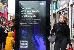 © Licensed to London News Pictures. 07/03/2020. London, UK. People walk past a Coronavirus public information campaign poster in London, which focuses on hand washing. Forty two more people have tested positive of the virus, taking the total to 206 in the UK. Photo credit: Dinendra Haria/LNP