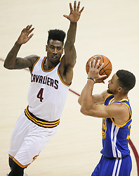 The Cleveland Cavaliers' Iman Shumpert (4) contests a 3-point shot by the Golden State Warriors' Stephen Curry three-pointer in the first quarter during Game 4 of the NBA Finals at Quicken Loans Arena in Cleveland on Friday, June 9, 2017. (Photo by Leah Klafczynski/Akron Beacon Journal/TNS) *** Please Use Credit from Credit Field ***