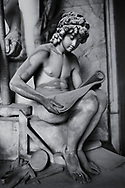 Heavens Gate - Black and white art photo of the stone sculptured monumental tomb for the Celesia Family by sculptor D. Paernio 1899.  An adolescent angel with delicate features is examining some sheets while sitting, representing so the Study.  Sculpted in the bourgeois Realism style this gigantic statue of the worker follows Michelangelo's heroic style, which was an obsession to many European and Italian sculptors between the end of the 19th century and the beginning of the 20th century,  Section A, no 51, The Staglieno Monumental Cemetery, Genoa, Italy .<br /> <br /> Visit our PEOPLE & PLACES PHOTO ART COLLECTIONS for more photos to buy as buy as wall art prints https://www.photoshelter.com/mem/images/index#/C00001WetsxVxNTo/ .<br /> <br /> Visit our LANDSCAPE PHOTO ART PRINT COLLECTIONS for more wall art photos to browse https://funkystock.photoshelter.com/gallery-collection/Places-Landscape-Photo-art-Prints-by-Photographer-Paul-Williams/C00001WetsxVxNTo