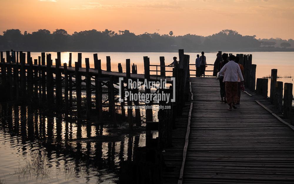 People across U Bein's Bridge near Amapura in Mandalay at sunrise
