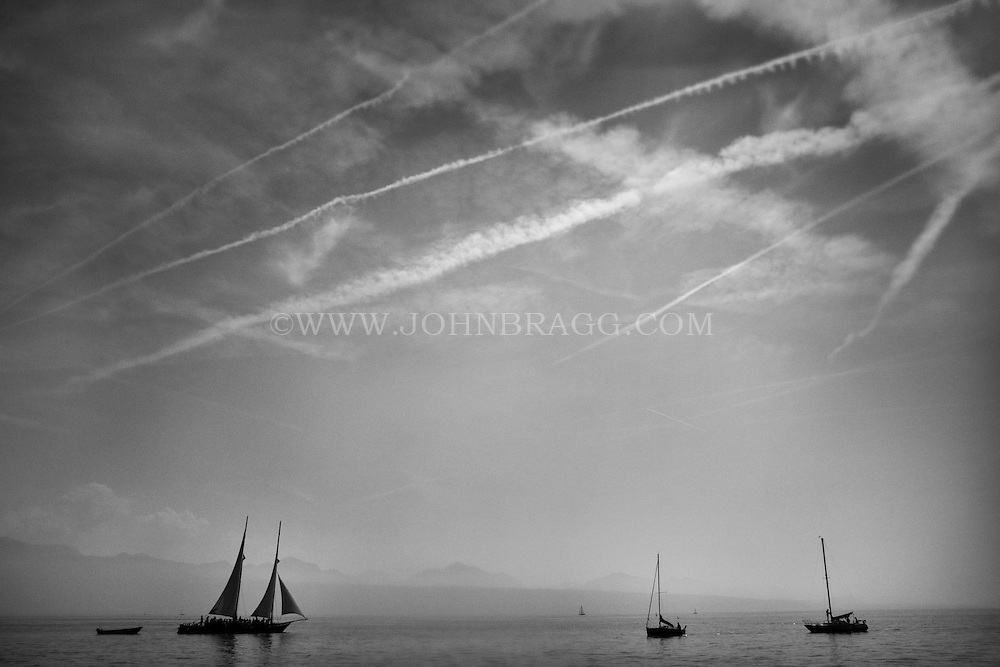 Black and white photo of sailboats out on Lake Geneva in Lausanne, Switzerland with a dramatic sky above.