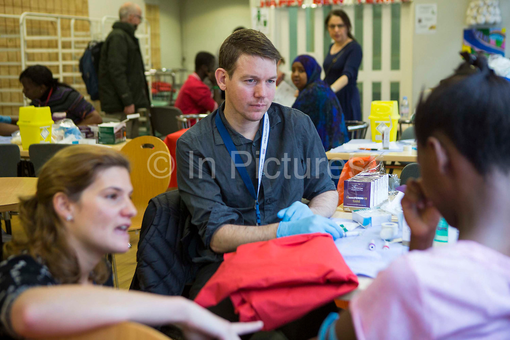 Two nurses try to reassure an anxious patient who is scared of needles and is reluctant to have a blood test as part of a tuberculosis (TB) contact screening exercise in a young people's hostel in Central London, UK.
