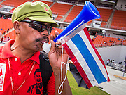 """19 NOVEMBER 2013 - BANGKOK, THAILAND: A Red Shirt supporter blows a horn to show his support for a speaker during a rally in Bangkok. As many as 30,000 """"Red Shirts"""" are expected in Bangkok this week ahead of a Thai court ruling that could cause the collapse of the government of Yingluck Shinawatra, the Prime Minister. The Red Shirts are gathering in a suburban sports stadium before marching to the court. The Red Shirts are mostly farmers and rural Thais who support the Shinawatra government.     PHOTO BY JACK KURTZ"""