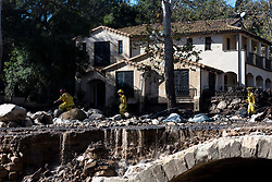 January 10, 2018 - U.S. - Firefighters tread on a destroyed Ashley Road after deadly mudslides swept through Montecito. (Credit Image: © Santa Barbara News-Press via ZUMA Wire)