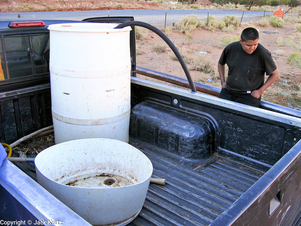 22 OCTOBER 2007 -- MONUMENT VALLEY, UT: AJ RYAN STANLEY, a Navajo Indian living on the Navajo reservation in northern Arizona, fills a 50 gallon water barrel with potable water at the well at Goulding's Trading Post in Monument Valley, UT. Stanley and his grandfather make daily trips to the well for potable water because they don't have a domestic water supply at their homestead. The well at Goulding's was first dug by Seventh Day Adventists missionaries  and is the only source of clean, free water for miles around. More than 30 percent of the homes on the Navajo Nation, about the size of West Virginia and the largest Indian reservation in the US, don't have indoor plumbing or a regular supply of domestic water. Many of these homes have to either buy water from commercial vendors or haul water from public wells. A Federal study showed that the total cost of hauling water was about $113 per 1,000 gallons. A Phoenix household, in comparison, pays just $5 a month for up to 7,400 gallons of water. The lack of water on the reservation means the Navajo are among the most miserly users of water in the United States. Families that have to buy or haul water use only about 15 gallons of water per day per person. In Phoenix, by comparison, the average water use is about 170 gallons per day.  Photo by Jack Kurtz/ZUMA Press