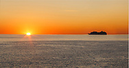A cruise ship heading toward anchorage at Bar Harbor just as the sun begins to peak over the horizon to start another gorgeous autumn day at Acadia National Park, Maine, USA