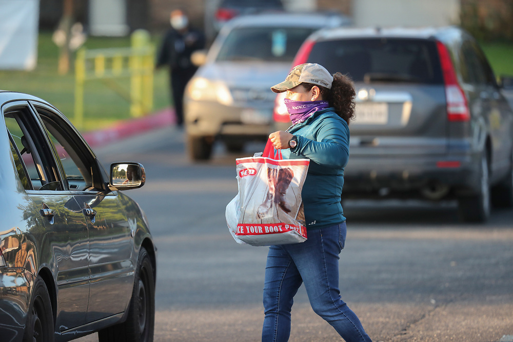 Staff members including Arlene Lozano (c)  help conduct a twice-weekly fresh food drive sponsored by Catholic Charities helping low-income Texans  make ends meet in Austin. The October 1, 2020 effort helped several hundred family members with fruit, meats, milk and cereal.