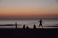 Before sunrise, early morning on a part of China beach in Danang. Silhouettes of five people on the beach. A man is stretching, threee women are seated looking at the sea and an old woman is walking along the beach.bicycles. He's looking at the sea.