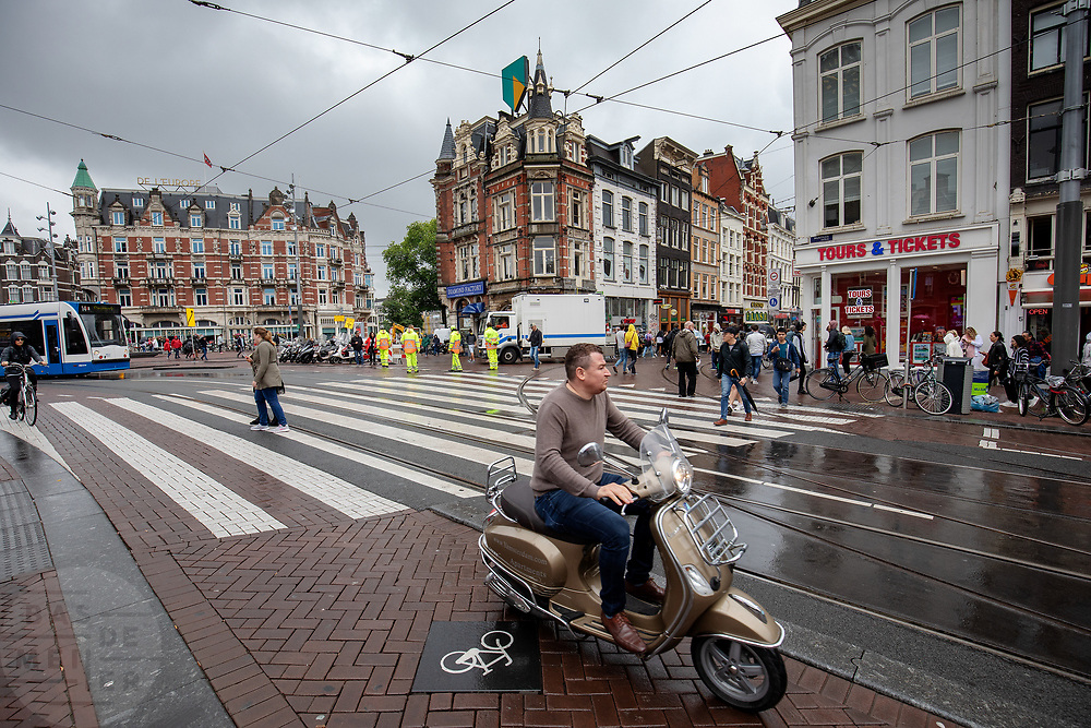 Een man op een snorscooter rijdt over het fietspad bij het Muntplein in Amsterdam.<br /> <br /> At the Munt Square in Amsterdam a man rides on a scooter on the bike lane.