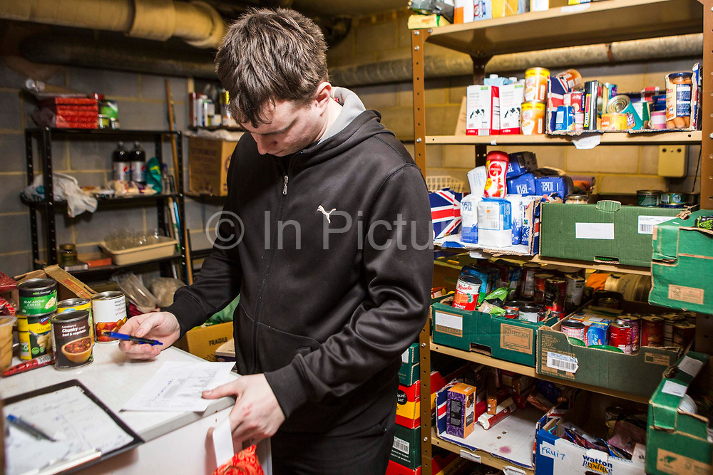 A Trussell Trust foodbank volunteer uses a checklist form to prepare an emergency food box for a family who are unable to provide enough food for their children in Kingston, United Kingdom.  Non-perishable and in-date food has been donated to the foodbank through schools, churches and individuals.  In 2012-13 foodbanks fed 346,992 people nationwide. Of those helped, 126,889 were children.  In response to the Government cuts to welfare, foodbanks have experienced a significant increase in demand and in September 2013, Kingston foodbank provided food for their 5,000th person.
