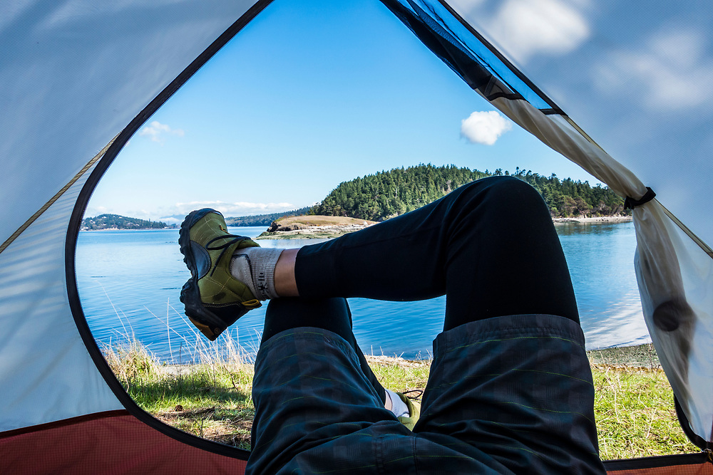 A first person point of view of a man's legs crossed in the entrance to a tent on Skagit Island, Washington, USA.
