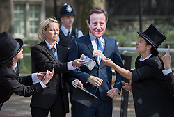 © Licensed to London News Pictures. 12/05/2016. London, UK. Police standby as a protestor dressed as Prime Minister David Cameron is offered fake money as he stands outside the anti-corruption summit. The real Mr Cameron is hosting a one day summit which is addressing world corruption. Photo credit: Peter Macdiarmid/LNP
