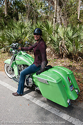 Laura Klock riding a green custom Harley-Davidson dresser through Tomoka State Park during Daytona Bike Week. FL, USA. March 11, 2014.  Photography ©2014 Michael Lichter.