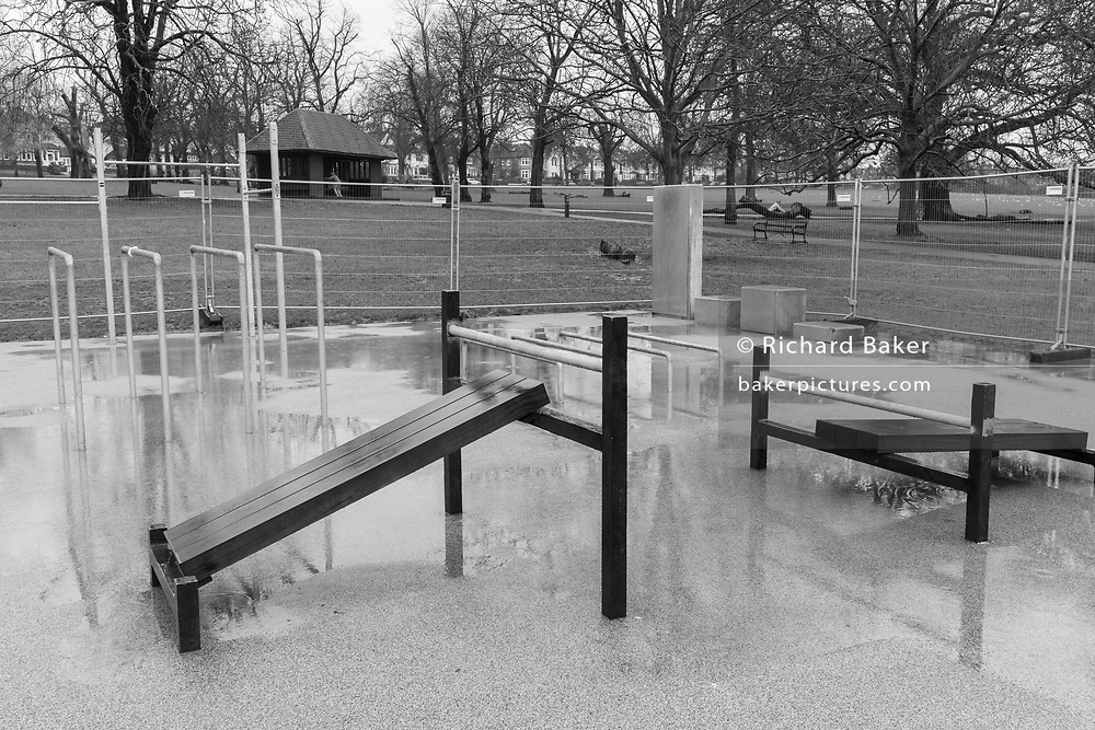 Ruskin Park's open-air gym, an outdoor exercise facility owned by Lambeth council in south London, remains closed-off on a cold and wet Saturday morning during the third lockdown of the Coronavirus pandemic, in on 30th January 2021, in London, England. Despite railings surrounding the closed-off area, the gym is still being used by those needing to use the bars and sit-up ramps.