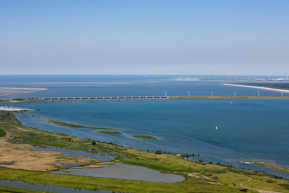 Nederland, Zuid-Holland, Haringvliet, 12-06-2009; Haringvlietsluizen en Haringvlietdam, gezien naar de tweede Maasvlakte. In de voorgrond natuurreservaat De Scheelhoek. De sluizen, onderdeel van de Deltawerken, zijn spuisluizen en zorgen er voor dat het zoete water uit het Haringvliet (rechts op de foto) zoals aangevoerd door Maas en Rijn geloosd kan worden. In het kader van modern natuurbeheer ('getemd getij') gaan de sluizen tegenwoordig bij eb én vloed beperkt open, om de getijden hun enigszin terug te laten komen in achterliggende estuarium .Dam and sluices between islands Voorne-Putten en Goeree-Overflakkee (bottom); the sluices are for draining water coming from the rivers Rhine and Maas (Meuse) from the natural bassin (right) to the North sea (left). Modern ecolical insight has led to opening the sluices semi-permanently, resulting in the estuary function of the Haringvliet patially being restored.Swart collectie, luchtfoto (25 procent toeslag); Swart Collection, aerial photo (additional fee required).foto Siebe Swart / photo Siebe Swart