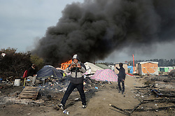 Smoke rises over the Calais Jungle camp, as several large fires broke out in the near deserted migrant camp in northern France on the third day of the operation to clear it.
