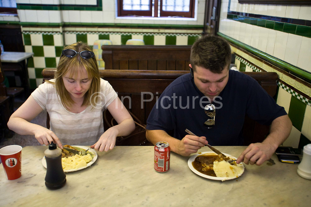 Customers eat lunch in Manze's Eel, Pie and Mash shop on Tower Bridge Road London, UK.This pie shop was opened in 1897 and is the oldest pie and eel shop in the countryEel, pie and mash shops are a traditional but dying business. Changing tastes and the scarcity of the eel has meant that the number of shops selling this traditional working class food has declined to just a handful mostly in east London. The shops were originally owned by one or two families with the earliest recorded, Manze's on Tower Bridge Road being the oldest surviving dating from 1908. Generally eels are sold cold and jellied and the meat pie and mash potato covered in a green sauce called liquor.