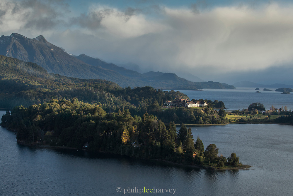 View of lakeshore next to forest by mountains in Lago Moreno, Bariloche, Argentina