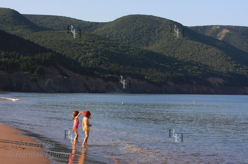 Two little girls wade in surf at Cabot's Landing Historic Site and Provincial Park, where Venetian John Cabot may have landed in 1497 and discovered North America for England; Cape Breton Island, Nova Scotia, Canada.