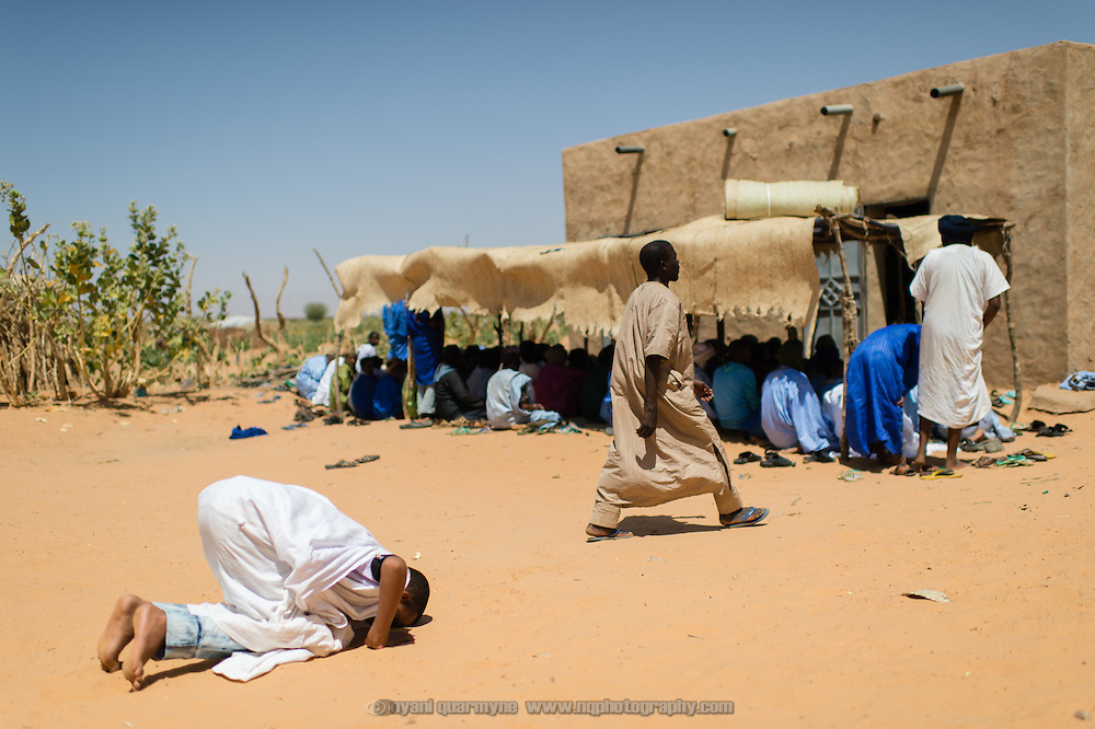 A man performing ritual prayers on entering the mosque compound in the village of Mbera, Mauritania on 8 March 2013. Though the mosque is located in the 'village' - the original site of a refugee camp for Malians fleeing conflict in Mali in the early 1990s - it now also serves the current Mbera refugee camp, which is home to approximately 70 000 refugees fleeing the current conflict.