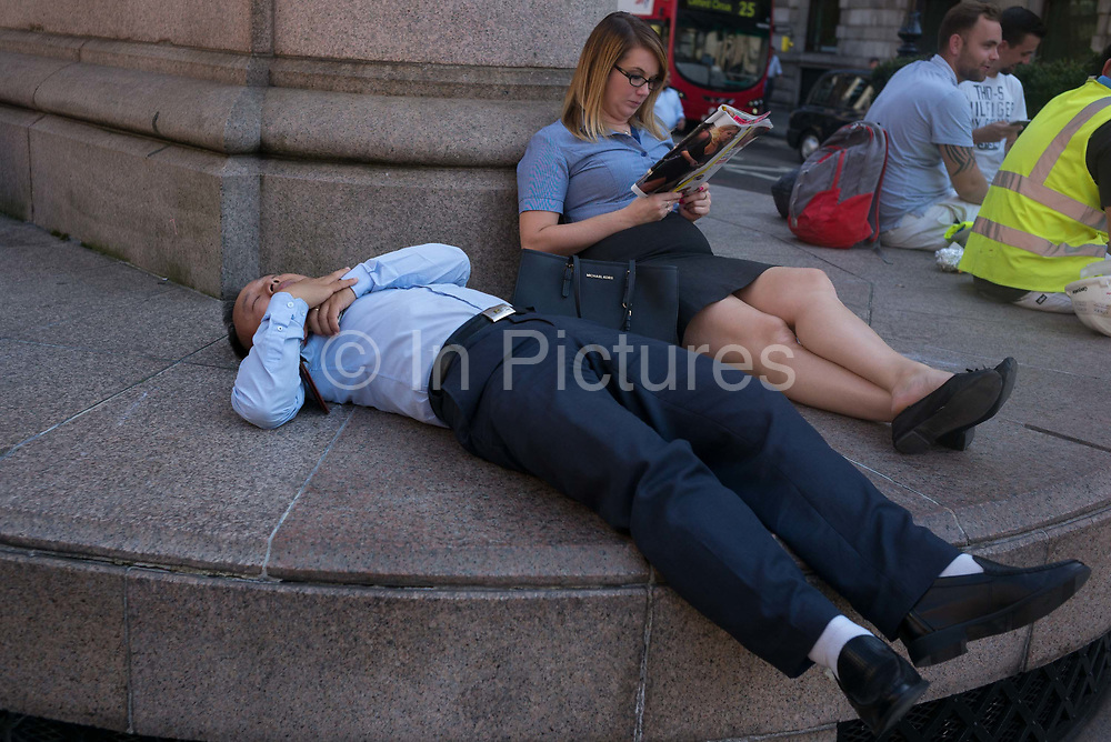 A City worker with others, sleeps on the plinth of a statue, outside in the afternoon during an unusual autumn heatwave on 13th September 2016, in the City of London, England.