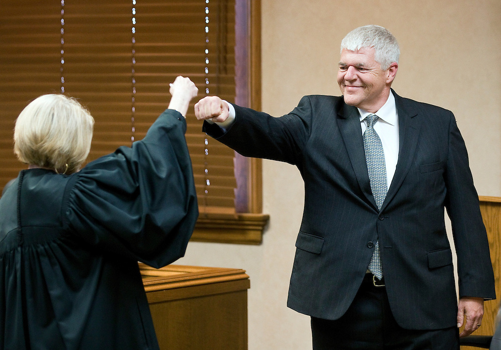 Judge Teresa K. Luther fist bumps Mark Young before Young is sworn in as 9th District Judge Friday at the Hall County Courthouse in Grand Island. Judge Luther spoke briefly at the beginning of the ceremony. (Independent/Matt Dixon)