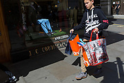 The blue legs of a mannequin in the window of a quality retailer and a young consumer clutching shopping bags from the retail brand Superdry, on 18th April 2017, in London, England.
