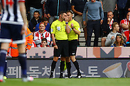 Referee Michael Oliver discusses a tackle with his assistant leading to Stoke city's Charlie Adam (not in pic) getting sent off.  Barclays Premier League match, Stoke city v West Bromwich Albion at the Britannia stadium in Stoke on Trent, Staffs on Saturday 29th August 2015.<br /> pic by Chris Stading, Andrew Orchard sports photography.