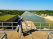 01 JULY 2015 - NONG BUA, LOPBURI, THAILAND: Maintenance workers at Pa Sak Dam. The spillway below them is normally full of water. Central Thailand is contending with drought. By one estimate, about 80 percent of Thailand's agricultural land is in drought like conditions and farmers have been told to stop planting new acreage of rice, the area's principal cash crop. Water in reservoirs are below 10 percent of their capacity, a record low. Water in some reservoirs is so low, water no longer flows through the slipways and instead has to be pumped out of the reservoir into irrigation canals. Farmers who have planted their rice crops are pumping water out of the irrigation canals in effort to save their crops. Homes have collapsed in some communities on the Chao Phraya River, the main water source for central Thailand, because water levels are so low the now exposed embankment is collapsing. This is normally the start of the rainy season, but so far there hasn't been any significant rain.     PHOTO BY JACK KURTZ