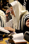 An Orthodox Jewish man belonging the Bobov Hasidism during Morning Prayer inside a Stamford Hill synagogue. Communal praying in a minyan (quorum) is preferred by men who wear a Tallit (prayer shawl) and a Tefillin (a box containing strips of parchment inscribed with 4 passages of the Torah) on their heads with the leather straps around their arm and hand.