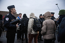 October 24, 2016 - Calais, France - Refugees arriving and waiting at the hangar of distribution of refugees with their luggage. The miners quickly pass into the hangar under the protection of associations that validate or not the inputs, in Calais, France on october 24, 2016. The dismantling of the jungle began Monday morning. Refugees come accompanied by the associations to the starting center ''C.A.O.''. Police frames the device. More than 850 press credentials were distributed. (Credit Image: © Julien Pitinome/NurPhoto via ZUMA Press)