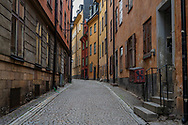 Colorful morning photo of a quiet side street in the Old Town section of Stockholm, Sweden.