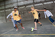 Young boys men teenagers playing football on a concrete pitch court, at La Casita home for disadvantaged or recovering street children, Buenos Aires, Argentina. This group were the Argentinian 'Street Child World Cup' team held in Rio de Janeiro in March 2014.