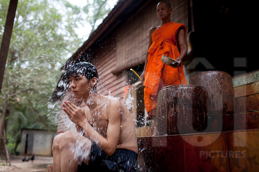 A monk gives a young man a holy bath in a traditional ritual, Angkor, Cambodia, Southeast Asia