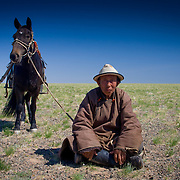 Old Mongolian man sits in Gobi Desert with horse (, Mongolia - Sep. 2008) (Image ID: 080906-1404121a)