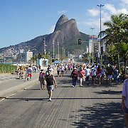 Walkers exercise early on Sunday morning at Ipanema Beach with the twin peaks of dois irmaos in the distance. On Sunday's the main roads along the beaches of Copacabana, Leblon and Ipanema are closed to traffic bringing out thousands of people of all ages to walk, run, jog, ride, skateboard and cycle more than 10 km of beachside roadway. Rio de Janeiro,  Brazil. 4th July 2010. Photo Tim Clayton....