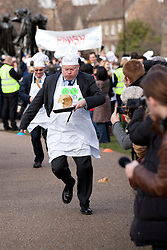 © Licensed to London News Pictures. 21/02/2012. LONDON, UK. Lord Kennedy, a Labour Peer, tosses a pancake and runs past crowds as he takes part in an annual pancake race outside the Houses of Parliament today (21/02/12). Lords, Members of Parliament and political journalists today took part in the 2012 'Rehab Parliamentary Pancake Race' in aid of disability charity Rehab. The parliamentary team took the trophy after an extra lap was run due to widespread cheating. Photo credit: Matt Cetti-Roberts/LNP