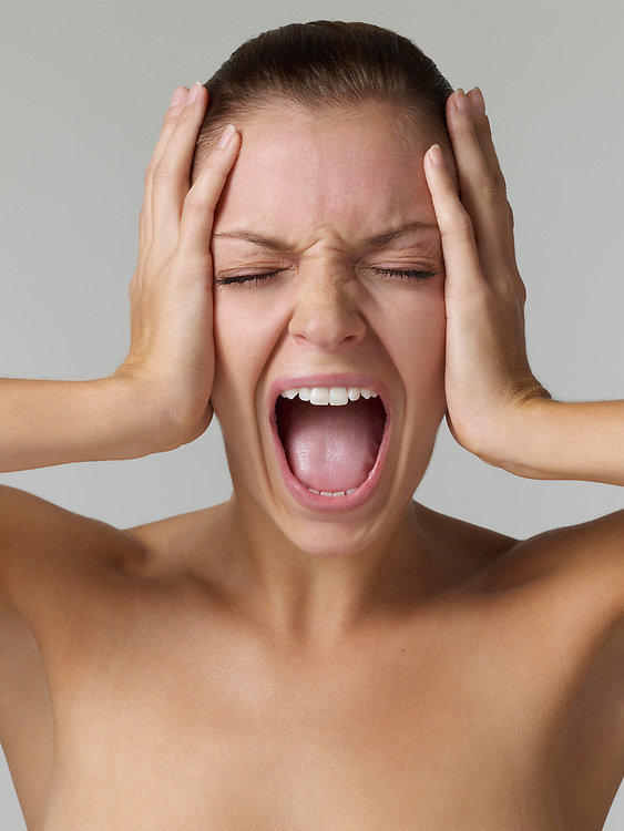 Head shot of woman holding her head, eyes closed and screaming