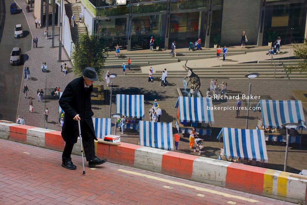 Elderly man walks bent past a regeneration project hoarding image at Elephant & Castle, London borough of Southwark.