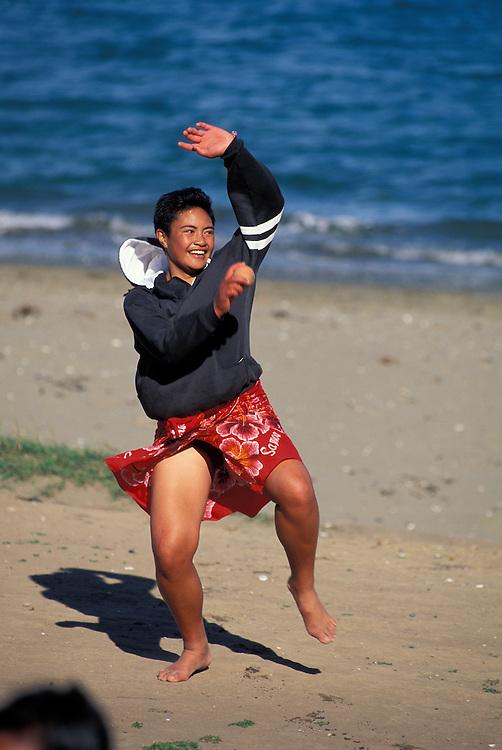 New Zealand, North Island, (MR) Serafina Akeli plays cricket with her family on  beach at Lyall Bay in Wellington