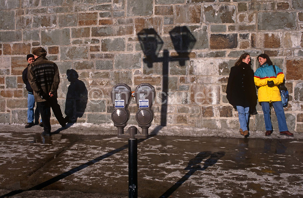 Friends chat near a parking meter and the shadow of street lighting on a city wall, on 11th January 1999, in Quebec City, Quebec, Canada.
