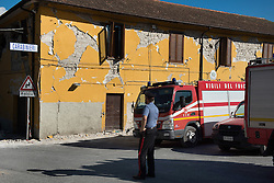 © London News Pictures. 25/08/2016. Amatrice, Italy. A policeman looks at a damaged police station in the town of Amatrice in central Italy where a 6.2-magnitude earthquake destroyed towns in the area. The death toll is currently at 247 with dozens of people still missing. Thousands of rescuers continue efforts to find survivors. Photo credit: Mario Sabatini/LNP